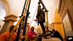 This Dec. 21, 2020 photo provided by the Office of the Governor of Virginia shows workers removing a statue of Confederate Gen. Robert E. Lee from the National Statuary Hall Collection in Washington.