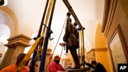 FILE - This Dec. 21, 2020 photo provided by the Office of the Governor of Virginia shows workers removing a statue of Confederate Gen. Robert E. Lee from the National Statuary Hall Collection in Washington.