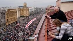 Pristalice beloruske opozicije sa krovova gledaju marš hiljada građana ka Trgu nezavisnosti u Minsku, 23. avgusta 2020.