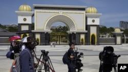 FILE - Journalists are seen gathered outside the National Palace, in Kuala Lumpur, Malaysia, Feb. 27, 2020.