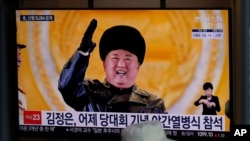 """A man wearing a face mask sits in front of a TV screen showing North Korean leader Kim Jong Un, at the Seoul Railway Station in Seoul, South Korea, Friday, Jan. 15, 2021. The letters read """"Kim Jong Un attended stage in Thursday night's parade…"""