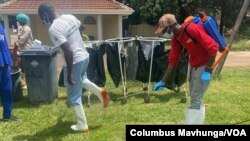 A health official sprays a colleague with a disinfectant Feb. 18, 2021, at Wilkins Hospital in Harare, where Zimbabwe launched its COVID-19 vaccination program. (Columbus Mavhunga/VOA)