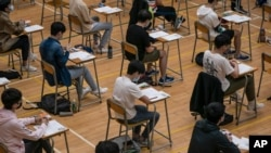 FILE - Students sit for the Diploma of Secondary Education (DSE) exams April 26, 2021, in Hong Kong.