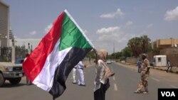 Hiba Salah waves Sudan's flag outside Friendship Hall as the agreement is being signed (E. Sarai/VOA)