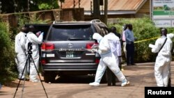 Forensic experts secure the scene of an attempted assassination on Ugandan minister of works and transport General Katumba Wamala, in the suburb of Kiasasi within Kampala, Uganda, June 1, 2021.