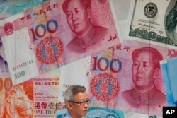 FILE - A man walks by an exchange shop decorated with Chinese yuan in Hong Kong, Aug. 6, 2019. China let the yuan sink to an 11-year low against the dollar after President Donald Trump threatened to block U.S. firms from doing business with China.