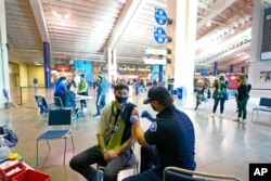 FILE - Austin Kennedy, left, a Seattle Sounders season ticket holder, gets the Johnson & Johnson COVID-19 vaccine at a clinic in a concourse at Lumen Field, May 2, 2021.