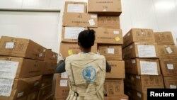 ARCHIVO - Un trabajador del Programa Mundial de Alimentos arregla paquetes de ayuda humanitaria a África para combatir el brote del coronavirus. Aeropuerto Internacional Addis Ababa, Etiopía.