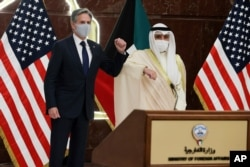 U.S. Secretary of State Antony Blinken and Kuwaiti Foreign Minister Sheikh Ahmed Nasser Al Mohammed Al Sabah bump elbows at their joint news conference at the Ministry of Foreign Affairs in Kuwait City, Kuwait, July 29, 2021.