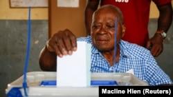 Un électeur dépose son bulletin de vote dans un bureau de vote lors des élections législatives à Abidjan, Côte d'Ivoire, le 6 mars 2021.