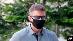 CORRECTS SOURCE - In this May 13, 2020, photo, Brian Dugan Yeargan, wearing a face mask and sunglasses, walks outside the Singapore State Court in Singapore. The 44-year-old American pilot has been jailed for four weeks for breaching a quarantine…