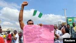 A demonstrator carries a banner during a protest demanding police reform in Lagos, Nigeria, Oct. 20, 2020.