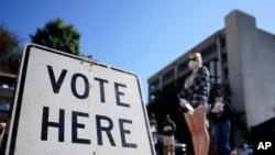 Los votantes hacen fila mientras esperan para votar temprano, el lunes 19 de octubre de 2020, en Athens, Georgia.