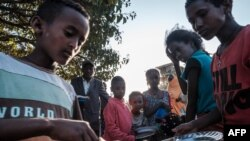 FILE - Displaced children from Western Tigray wait to receive food outside a classroom in the school where they are sheltering in Tigray's capital, Mekele, Feb. 24, 2021. Hunger and sexual violence have continued to rise dramatically since then.