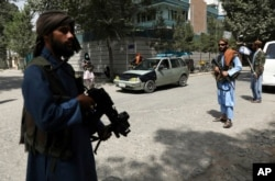 FILE - Taliban fighters stand guard at a checkpoint in the Wazir Akbar Khan neighborhood in the city of Kabul, Afghanistan, Aug. 18, 2021.