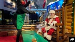 LaToya Booker limpia una barrera transparente entre los visitantes y Santa en la tienda Bass Pro Shop en Bridgeport, Connecticut.