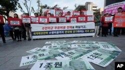 Các tờ tiền giả với hình ảnh Tổng thống Mỹ Donald Trump được bày trên đường trong khi những người biểu tình tụ tập gần Sứ quán Mỹ ở Seoul để phản đối yêu cầu của Mỹ đòi Seoul tăng chi để binh lính Mỹ đồn trú ở đây.