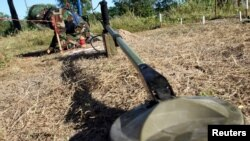 FILE - A deminer works near a metal detector at a testing area in a minefield during a demonstration to the media at the Demining Center in Kampong Speu province, Nov. 27, 2011.