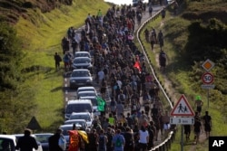 Anti-G-7 activists march along a road near a tent camp near Hendaye, France, Aug. 23, 2019.