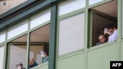 지난달 28일 신종 코로나바이러스 감염으로 30여명의 사망자가 발생한 이탈리아 알비노의 양로원에서 노인과 의료진들이 창밖을 보고 있다.