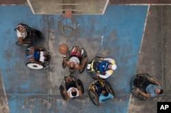 Manuel Mendoza juega baloncesto con sus amigos en silla de ruedas en una cancha pública en el barrio Artigas de Caracas, el 24 de octubre de 2020.