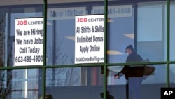 FILE - A woman walks past the signs of an employment agency, in Manchester, N.H., March 2, 2021.
