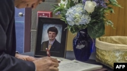 지난 2017년 6월 22일 미국 오하이오주 와이오밍의 와이오밍고등학교에서 열린 오토 웜비어 씨의 장례식에서 조문객이 웜비어 씨의 사진 옆에 놓인 방문객에 이름을 적고 있다.