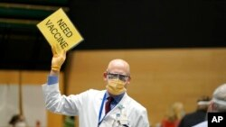 "FILE - Dr. John Corman, the chief clinical officer for Virginia Mason Franciscan Health, holds a sign that reads ""Need Vaccine"" to signal workers to bring him more doses of the Pfizer vaccine for COVID-19, Jan. 24, 2021."