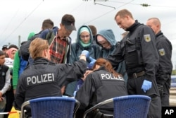 FILE - German policemen register refugees at the rail station in Freilassing, southern Germany, Sept. 14, 2015, before they take them away in busses.