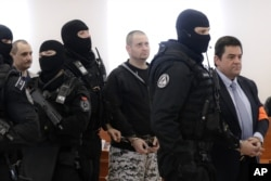 FILE - Suspects in the 2018 slaying of investigative journalist Jan Kuciak and his fiancee Martina Kusnirova are escorted by armed police officers from a courtroom in Pezinok, Slovakia, Dec. 19, 2019.