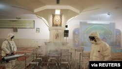 FILE - Members of a medical team spray disinfectant to sanitize indoor place of Imam Reza's holy shrine, following the coronavirus outbreak, in Mashhad, Iran, Feb. 27, 2020.