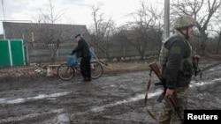 Seorang pria mendorong sepeda melewati seorang tentara yang berjaga di sebuah jalan di Novhorodske, Wilayah Donetsk, Ukraina, 3 Maret 2021.