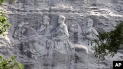 FILE - This June 23, 2015 file photo shows a carving depicting Confederate Civil War figures Stonewall Jackson, Robert E. Lee and Jefferson Davis, in Stone Mountain, Ga. The sculpture is America's largest Confederate memorial. (AP Photo/John…