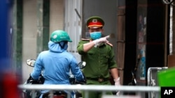Seorang polisi berbicara dengan seorang perempuan di pintu masuk barikade di mana salah satu warganya diduga memiliki Covid-19 di Hanoi, Vietnam, Rabu, 29 Juli 2020. (Foto: dok).