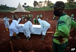 Workers lower a coffin containing the body of a suspected COVID-19 victim into a grave during a burial at the special section of Pondok Ranggon cemetery during coronavirus outbreak, in Jakarta, Indonesia, Sept. 24, 2020.