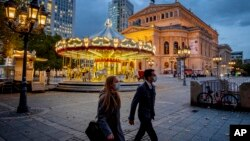 People wearing face masks walk past a carousel and the Old Opera in Frankfurt, Germany, Wednesday, Oct. 28, 2020. To avoid the further outspreads of the Coronavirus new restriction will be valid from next Monday. (AP Photo/Michael Probst)