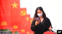 FILE - A woman wearing a face mask looks at her phone in Hanoi, Vietnam, Jan. 23, 2021. Vietnam says it has discovered a new coronavirus variant that's a hybrid of strains first found in India and the U.K. (Reuters)