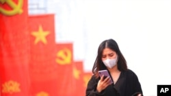 FILE - A woman wearing a face mask looks at her phone in Hanoi, Vietnam, Jan. 23, 2021. Vietnam says it has discovered a new coronavirus variant that's a hybrid of strains first found in India and the U.K.