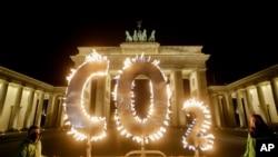 """环保组织""""绿色和平""""在德国柏林一个烛光组成的""""CO2""""字母前抗议气候变化,要求德国政府采取措施减排温室气体。(美联社 2021年5月6日)"""
