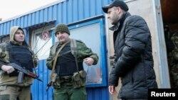 29일 우크라이나와 친러시아 반군의 포로 교환 현장에서 경계 병력이 한 남성을 인도하고 있다.