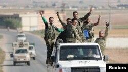 Kombatan pemberontak Suriah yang didukung Turki berkendara dekat perbatasan Kota Tal Abyad, Suriah, 22 Oktober 2019.