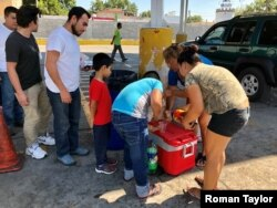 Central American migrants line up for community-donated food and drinks near the Puente Numero I International Bridge in Nuevo Laredo, Mexico. (R. Taylor/VOA)