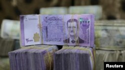 FILE - Syrian pounds are pictured inside an exchange currency shop in Azaz, Syria, Feb. 3, 2020. Rising prices and a drop in the currency's value have pushed ordinary Syrians to vent their anger in recent protests.