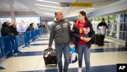 Mohammed Hafar, a la izquierda, ayuda a su hija Jana a llevar su equipaje mientras salen del aeropuerto JFK de Nueva York, el 3 de diciembre de 2019 (Foto: AP)