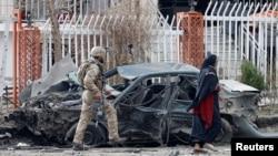 سیکیورٹی فورسز کا ایک اہل کار دہشت گرد حملے کا نشانہ بننے والی گاڑی کا معائنہ کر رہا ہے۔ 20 دسمبر 2020