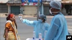 بھارتی شہر احمد آباد میں ہیلتھ ورکز لاک ڈاؤن کے دوران ایک خاتون کا ٹمپریچر چیک کر رہے ہیں۔