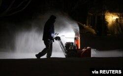 Roger Hake recibe ayuda de las luces de su camión mientras quita la nieve de la entrada antes de que salga el sol en Webster, cerca de Rochester, Nueva York, EE.UU., el 16 de febrero de 2021. Jamie Germano / Rochester Democrat y Chronicle / USA Today