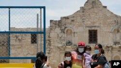 Visitantes posan frente a la fachada del Álamo, en San Antonio, Texas, mientras portan tapabocas. Los casos de COVID-19 se han elevado en Texas y el gobernador animó a las personas a usar tapabocas en espacios públicos.