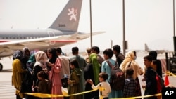 In this photo provided by the U.S. Marine Corps, civilians prepare to board a plane during an evacuation at Hamid Karzai International Airport, Kabul, Afghanistan, Aug. 18, 2021. (Staff Sgt. Victor Mancilla/U.S. Marine Corps via AP)