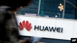 FILE - A woman walks by a Huawei retail store in Beijing, July 30, 2019.